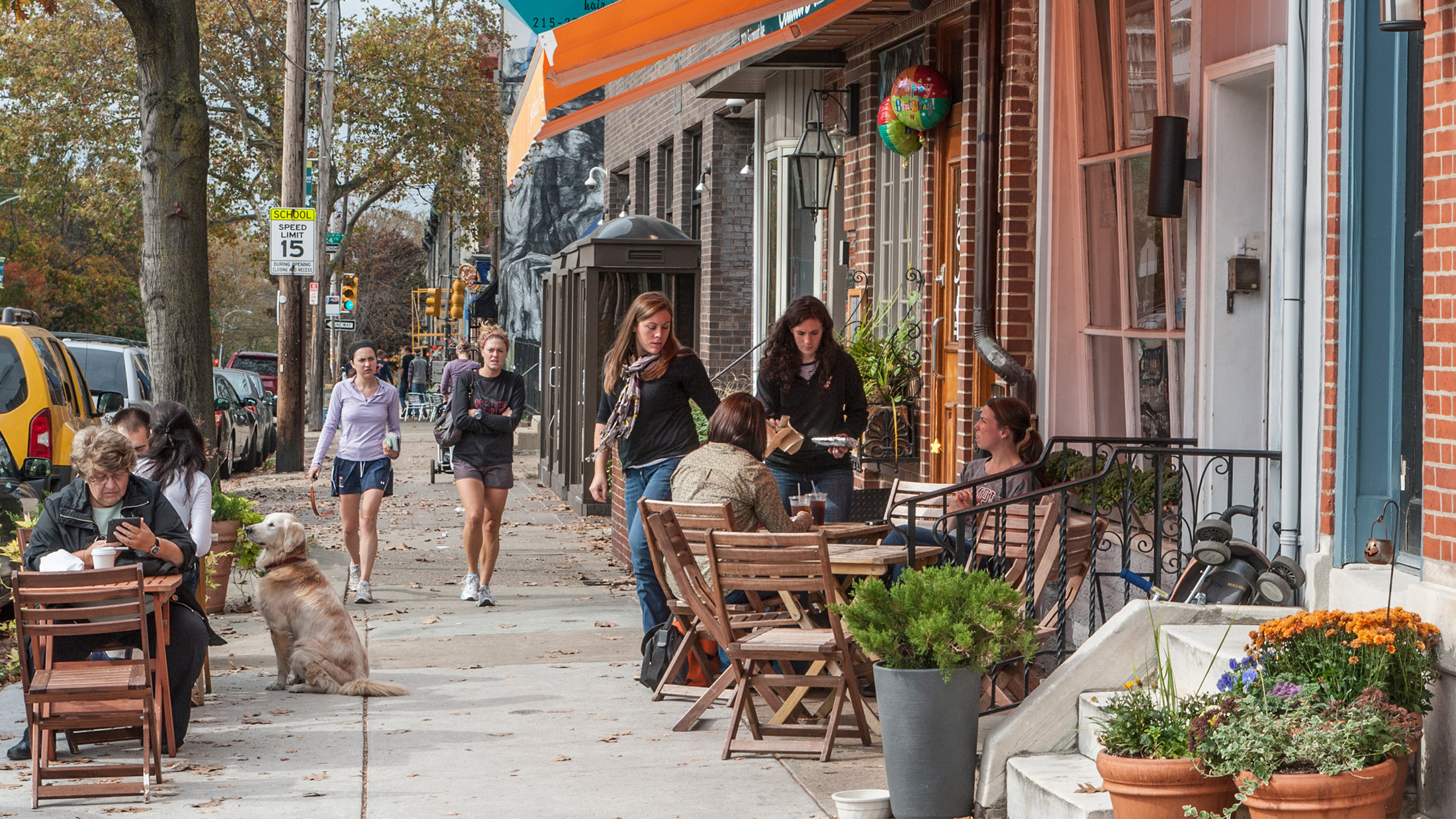 People walking and dining outside on a street in Fairmount